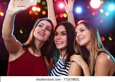 Smiling girls with smartphone taking selfie in a night club