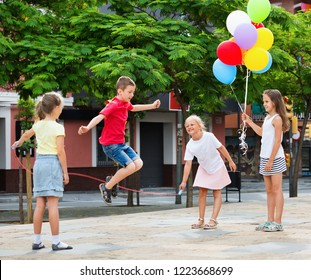 Smiling glad cheerful kids in school age playing together with jumping rope outdoors