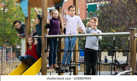 Smiling  glad children in school age sliding down together on playground's construction at street