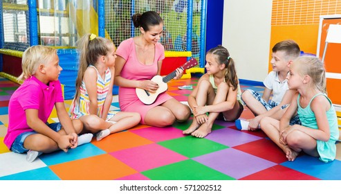 Smiling glad children sitting with teacher holding ukulele and listening to music in class at school