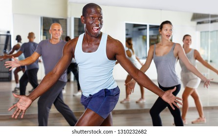 Smiling glad friendly  people practicing vigorous lindy hop movements in dance class