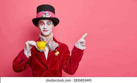 Smiling glad hatter in fashionable costume has aristocratic manners drinks tea and indicates at copy space isolated over rosy background. Man has image of classic tale character for halloween