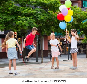 Smiling glad kids in school age playing together with jumping rope outdoors