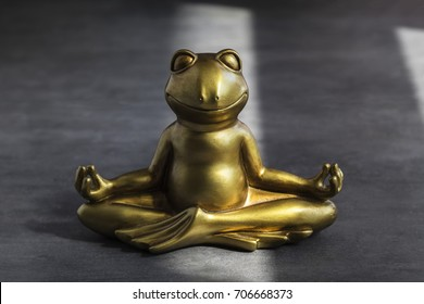 Smiling gold yoga frog meditating in lotus pose. Peace of mind, body and soul, balance and harmony concept.
