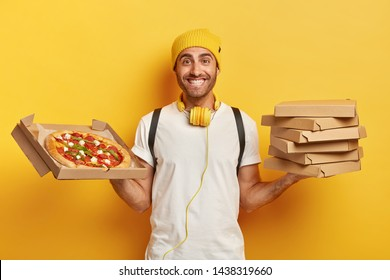 Smiling good looking deliveryman greets customer in friendly mannner, dressed neatly and maintains high level of hygiene, carries stack of containers with delicious appetizing pizza, carries backpack