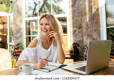 Smiling gorgeous businesswoman having pleasant phone conversation by mobile phone, woman taking notes, while sitting at the table, at the cafe, outdoors.