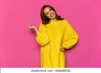 Smiling gorgeous girl, looking at camera, posing. Standing in stylish yellow sweater, on pink background. Concept of Valentine's day.
