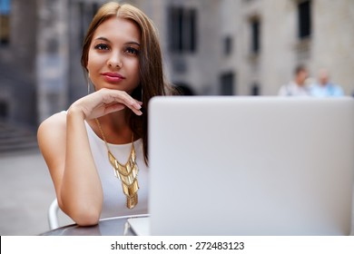 Smiling gorgeous woman sitting at street coffee shop looking to you, businesswoman sitting with open notebook next to her, female student read digital book on laptop computer sitting in sidewalk cafe
