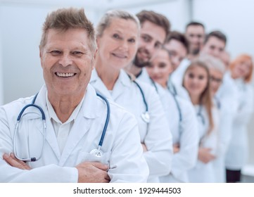 smiling GP standing in front of a group of doctors.