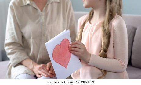 Smiling granddaughter gifting handmade greeting card with heart to grandmom