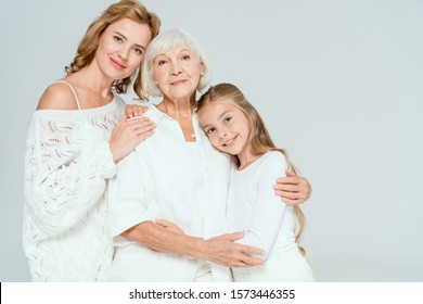 smiling granddaughter, mother and grandmother hugging isolated on grey