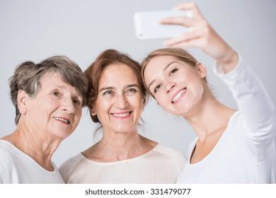 Smiling granddaughter taking perfect family selfie - horizontal view