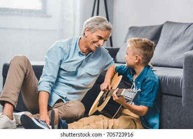 smiling grandfather and grandson playing on acoustic guitar while sitting on floor at home