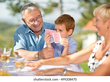 Smiling Grandfather playing cards with grandson outdoor