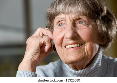 Smiling grandmother (80s) with cellphone. Studio picture