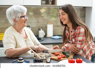 Smiling grandmother with granddaughter cooking in the kitchen.