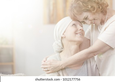 Smiling grandmother hugging sick but happy woman with cancer