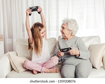 Smiling grandmother with little granddaughter playing games together with gamepads