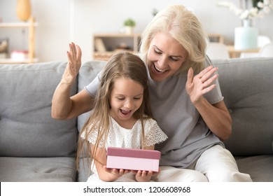 Smiling grandmother making surprise to cute little granddaughter giving gift box, excited small girl get birthday present from granny, happy older and younger generation celebrate at home together