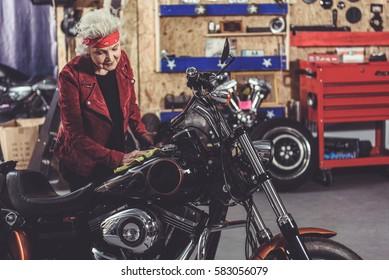 Smiling grandmother polishing bike in mechanic shop