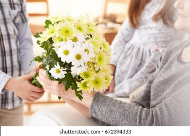 Smiling grandmother receiving bouquet of beautiful flowers from young grandson