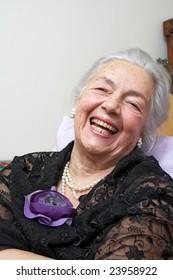 Smiling grandmother with silk violet rose