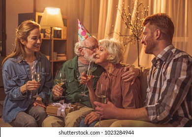 Smiling grandpa kissing cheerful grandmother in check. Outgoing relatives tasting alcohol on sofa. Love concept