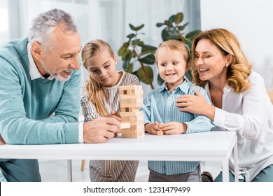 smiling grandparents and grandchildren playing blocks wood tower game together at home