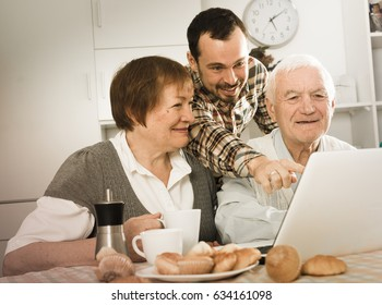 Smiling grandparents and grandson look interesting news on Internet on laptop at home