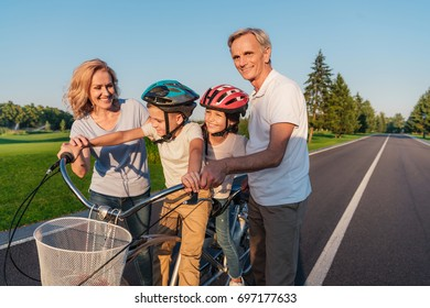 smiling grandparents helping little children in helmets ride bicycle in park