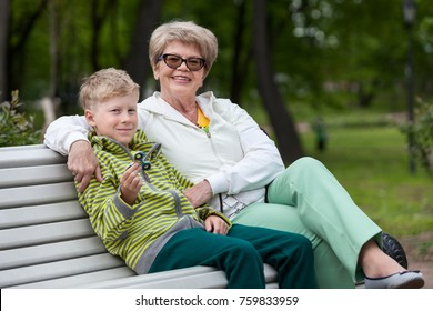 Smiling grandson playing with spinner gadget, happy grandma hugging boy