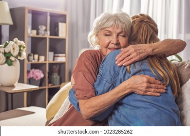 Smiling granny hugging girl in room. They sitting on sofa. Friendly relationship concept