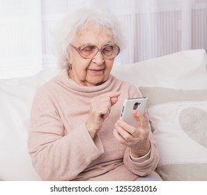 Smiling great-grandmother talking by smartphone