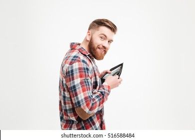 Smiling greedy man in plaid shirt putting money in his wallet over white background
