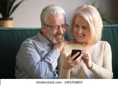 Smiling grey haired husband and blond wife sitting on sofa in living room using smart phone, mature family browsing internet reading media website, elderly couple and modern technologies usage concept
