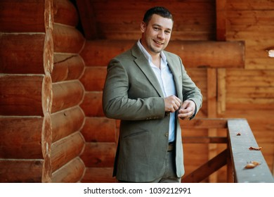 Smiling groom in the suit on the wooden balcony