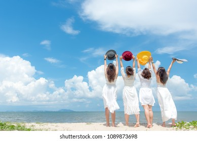 Smiling group asian woman wearing fashion white dress summer walking the sandy sea beach, blue sky sunshine background.  Happy tourist woman enjoy and relax serenity vacation. Lifestyle and Travel