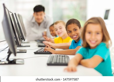 smiling group children in computer class with teacher on background