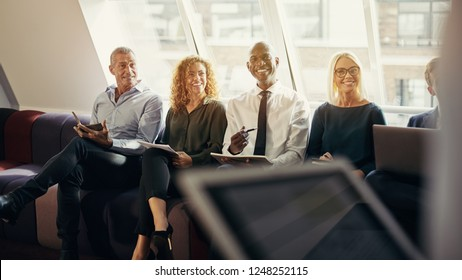 Smiling group of diverse businessmen and businesswomen sitting together on a sofa in an office during a presentation
