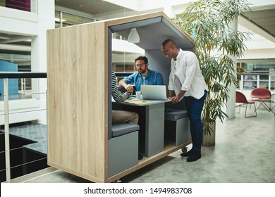 Smiling group of diverse businessmen working together on a project in a meeting pod in the lobby of a modern office
