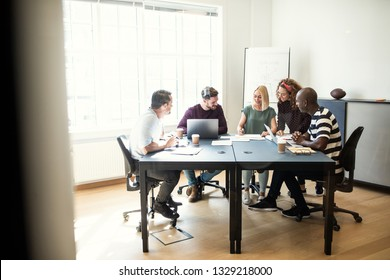 Smiling group of diverse designers working together on a project while sitting around a boardroom table in an office