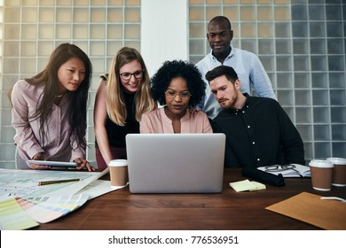 Smiling group of diverse work colleagues talking and working together on a laptop at a table in a modern office