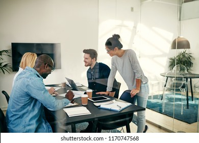 Smiling group of diverse young business colleagues discussing work together during a meeting inside of an office boardroom