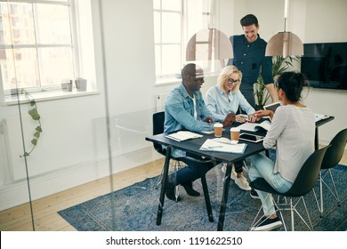Smiling group of diverse young businesspeople working around a table in the boardroom of a modern office discussing a project together