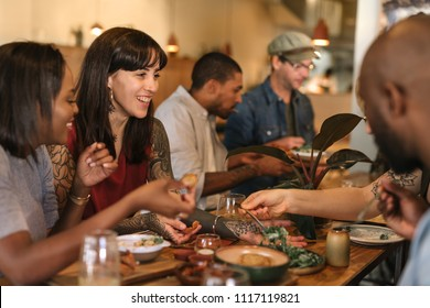 Smiling group of diverse young friends sitting at a table in a trendy bistro enjoying a meal together