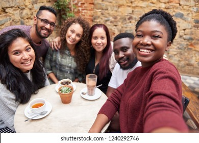 Smiling group of diverse young friends sitting around a table in the courtyard of a trendy cafe taking a selfie together