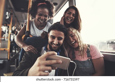 Smiling group of diverse young friends listening to music together on a smartphone while riding on a bus