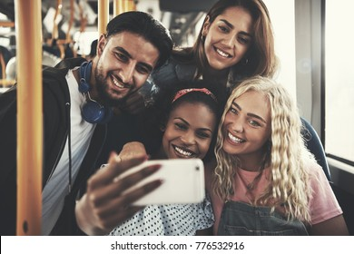 Smiling group of diverse young friends riding on a bus taking selfies together with a smartphone