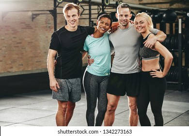 Smiling group of fit friends in sportswear standing arm in arm together after a workout class in a gym