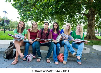 Smiling group of five high school girls and one boy sitting on a bench holding books. Horizontally framed photo.